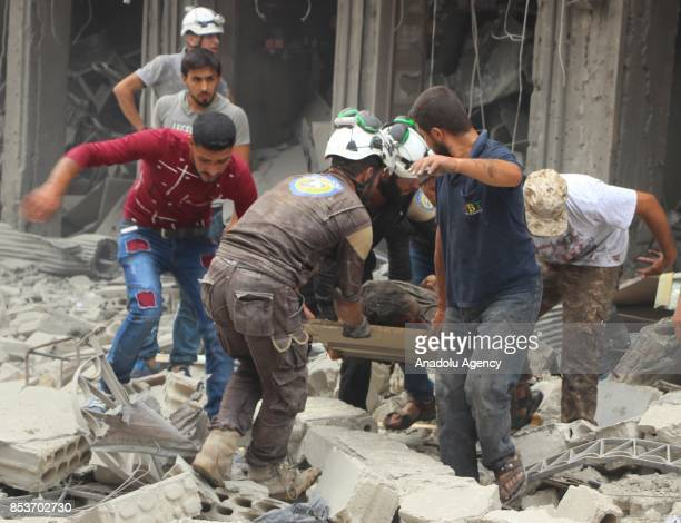 Search and rescue members and people carry an injured man to an ambulance after Assad Regime's forces carried out air strikes over the deconflict...