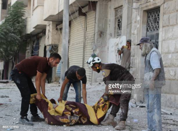 Search and rescue members and people carry an man to an ambulance after Assad Regime's forces carried out air strikes over the deconflict zone at the...