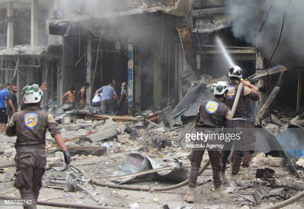 Search and rescue members try to extinguish burning store after Assad Regime's forces carried out air strikes over the deconflict zone at the Jisr...