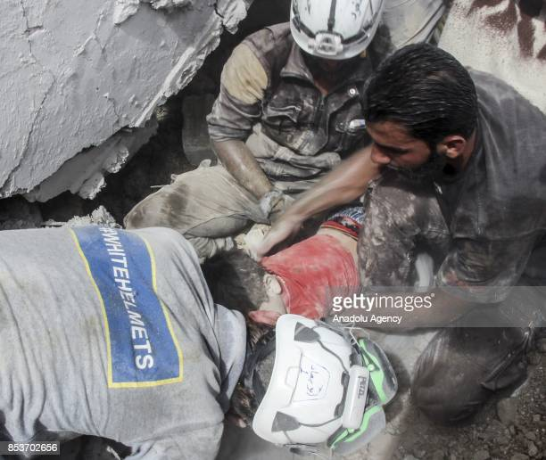 Search and rescue members try to rescue a kid under the debris of a building after Assad Regime's forces carried out air strikes over the deconflict...