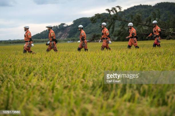 Search and rescue officers walk through a field after working at the site of a farm destroyed by a landslide triggered by an earthquake on September...