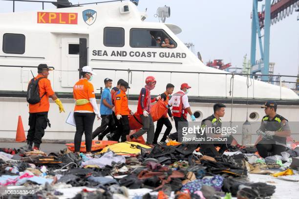 Search and Rescue personnel carry a body bag as they recovered debris and personal items from Lion Air flight JT 610 at the Tanjung Priok port on...