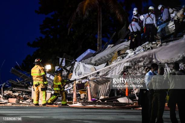 Search and Rescue personnel work as Miami Dade firefighters spray waterat a partial collapse building in Surfside, Miami Beach, on June 24, 2021. - A...