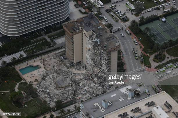 Search and rescue personnel work in the rubble of the 12-story condo tower that crumbled to the ground during a partially collapse of the building on...