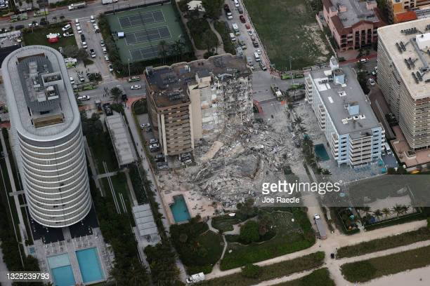 Search and rescue personnel work in the rubble of the 12-story condo tower that crumbled to the ground after a partial collapse of the building on...