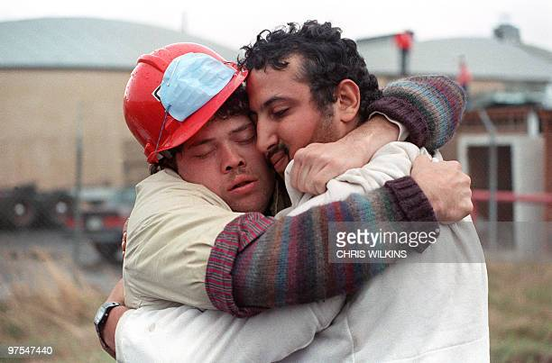 Search and rescue support workers Tim Schilwachder and Mamdouch Shabaan embrace 21 October 1989 by the Cypress Structure above 28th and Cypress Sts,...