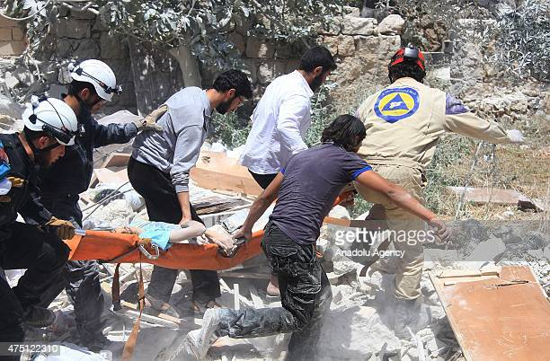 Search and rescue team accompanied with local people inspect rubble carry body of an Syrian among the building after Syrian army stage a barrel bomb...