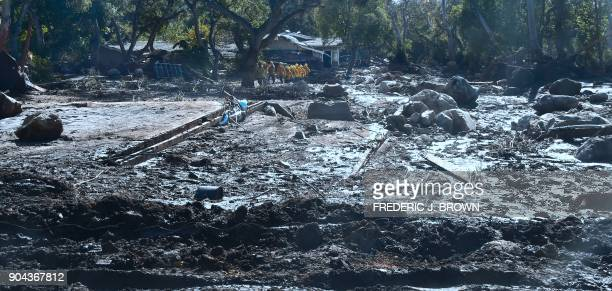 A search and rescue team make their way up a mud covered hillside in Montecito California on January 12 2018 Heavy rains on January 9 sent rivers of...