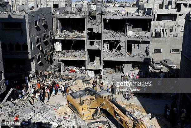 Search and rescue team members accompanied Palestinian local residents inspect the rubble of a destroyed house after it was hit by an Israeli...