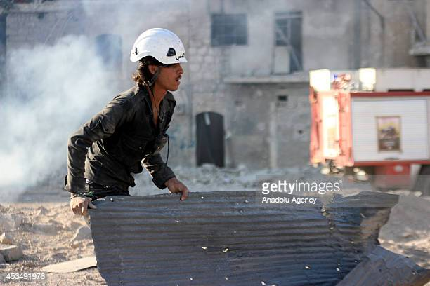 Search and rescue team members accompanied Syrian local residents search at the wreckage of buildings following Syrian regime helicopters dropped...