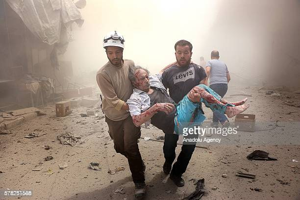 Search and rescue team members carry a man after Syrian regime airstrikes targeted the Meshed neighborhood of Aleppo Syria on July 21 2016