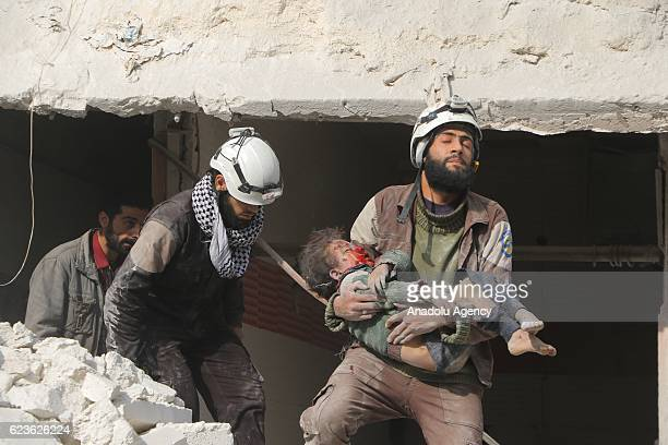 Search and rescue team members carry a wounded kid after war crafts belonging to the Syrian and Russian army carried out airstrikes over residential...