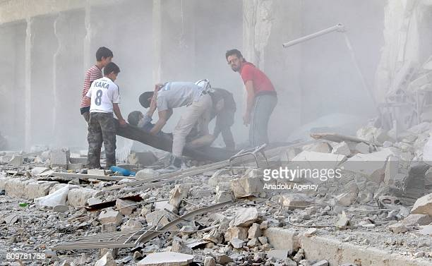 Search and rescue team members evacuate casualties from the rubbles after the Syrian regime forces airstrikes hit Aleppo's opposition controlled...