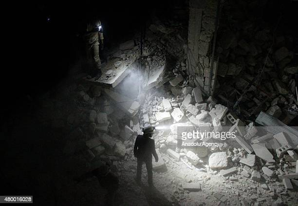 Search and rescue team members inspect collapsed buildings after Asad Regime forces' attack on residential areas in Karm al-Beik region of Aleppo,...