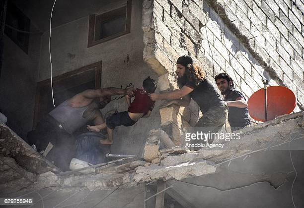 Search and rescue team members rescue a child from the debris of buildings after the barrel bomb attack staged by Syrian army in the...