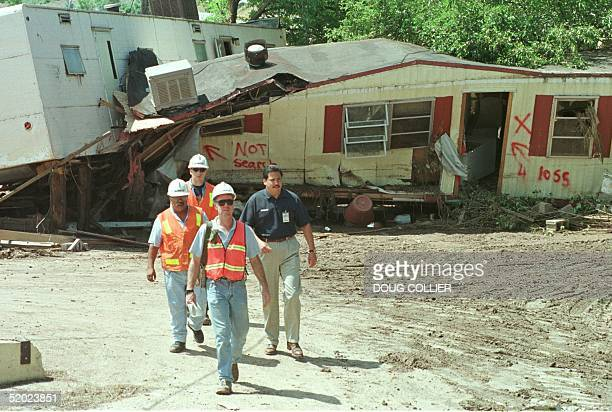 Search and Rescue team members walk past two damaged mobile homes at the South College Trailer Park in Fort Collins CO 30 July as search efforts for...