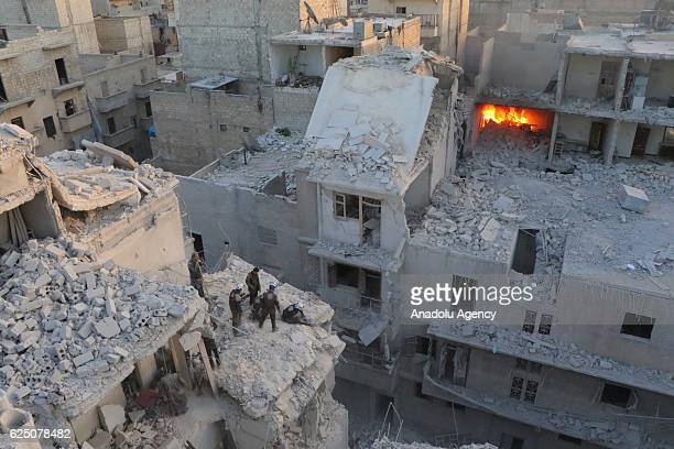 Search and rescue team members work at the scene of the air strikes carried out by the war crafts belonging to Assad regime forces on the...