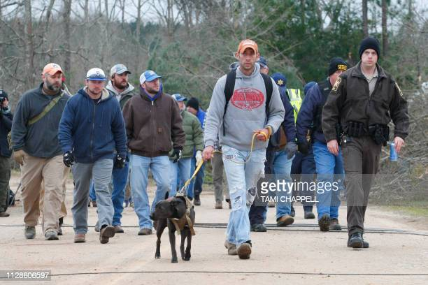 A search and rescue team walk past damage from a tornado which killed at least 23 people in Beauregard Alabama on March 4 2019 Rescuers in Alabama...