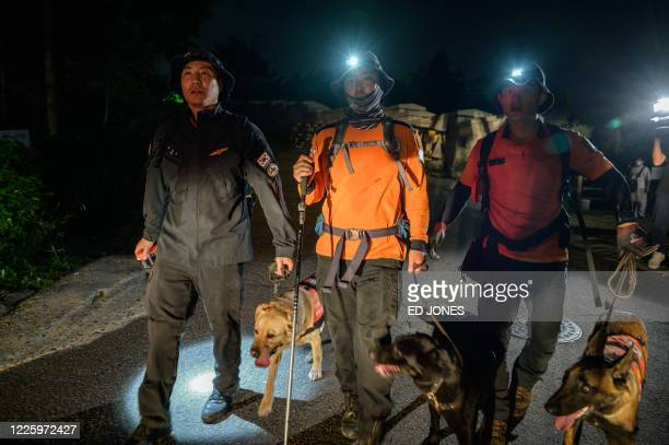 Search and rescue team walk with their dogs away from the park area where the body of Seoul Mayor Park Won-soon was discovered following reports that...