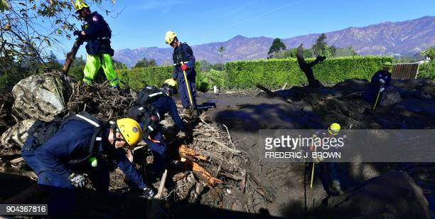 A search and rescue team work amid uprooted trees and rocks on mud in Montecito California on January 12 2018 Heavy rains on January 9 sent rivers of...