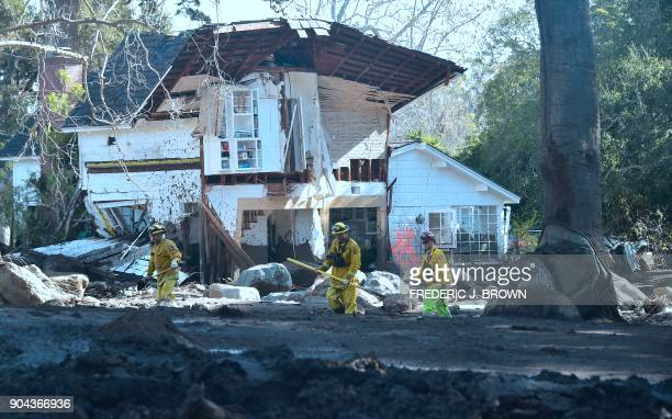 Search and rescue team workers walk past a demolished property in Montecito California on January 12 2018 Heavy rains on January 9 sent rivers of...