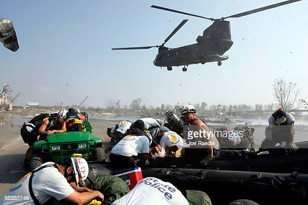Search and Rescue teams take cover as a US Army Chinook helicopter lands to pick them up after they spent the day looking for bodies in homes...