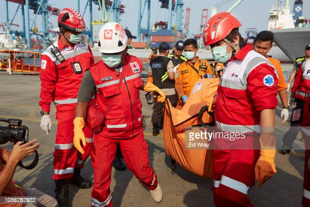 Search and rescue workers carry the remains of a victim of the Lion Air flight JT 610 crash at the Tanjung Priok port on November 2 2018 in Jakarta...
