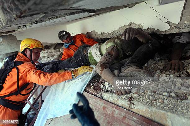 Search and Rescue workers from Mexico work on removing bodies trapped under the rubble of what is left of the building after the massive earthquake...