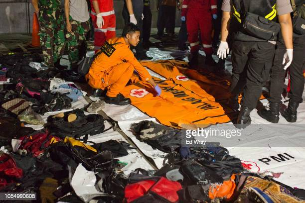 Search and rescue workers sits near a body bag and personal belongings of victims of Lion Air flight JT 610 at the Tanjung Priok port on October 29...
