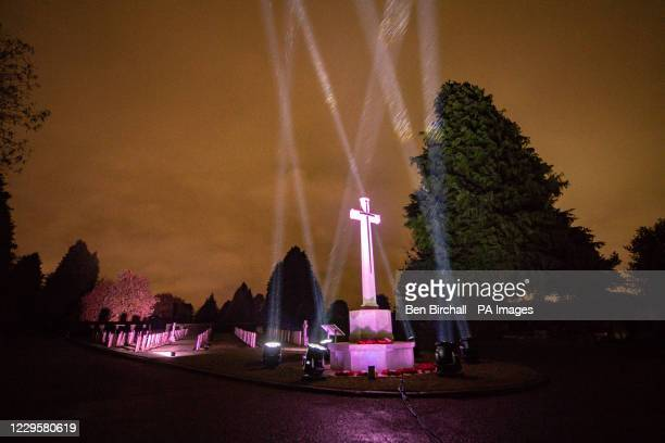 Searchlights in the night sky over the Commonwealth War Graves Commission cemetery at Cathays Cemetry, Cardiff, Wales, to remember the war dead on...
