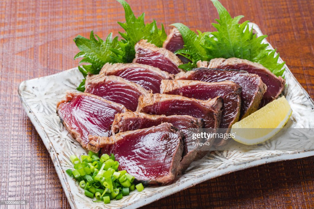Seared bonito slices on wood grain background : Stock Photo