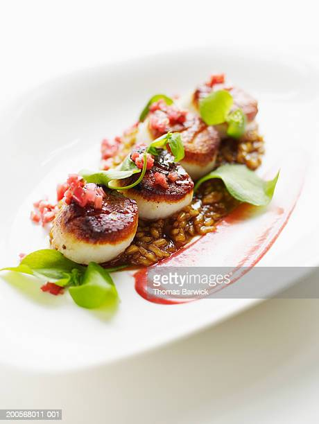seared rare scallops with sweet onion risotto and rhubarb - seared stock photos and pictures