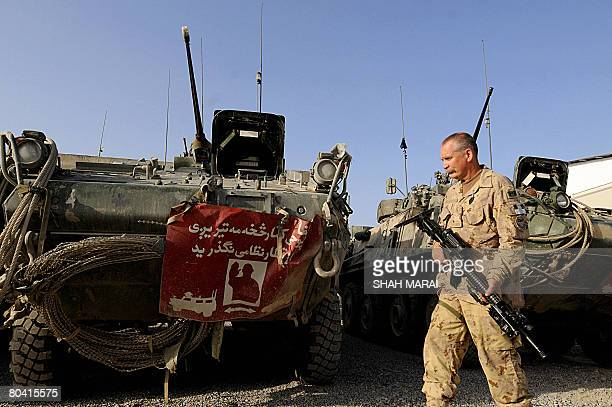 Seargent Malcolm Thomson a Canadian soldier with the NATOled International Security Assistance Force walks past patrol vehicles at the base of the...