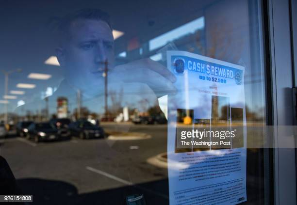 Seargent Mike Ebaugh with the Prince George's County police department's robbery unit posts a reward sign for information about commerical armed...