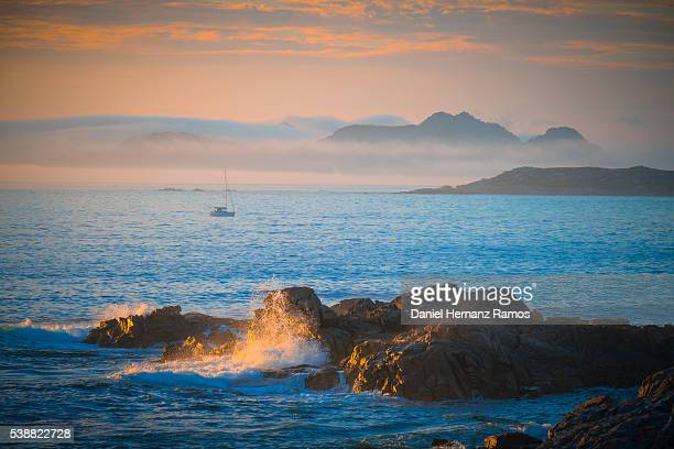 Seascape in Baiona (Bayona) with a boat and mountains in the background at sunset