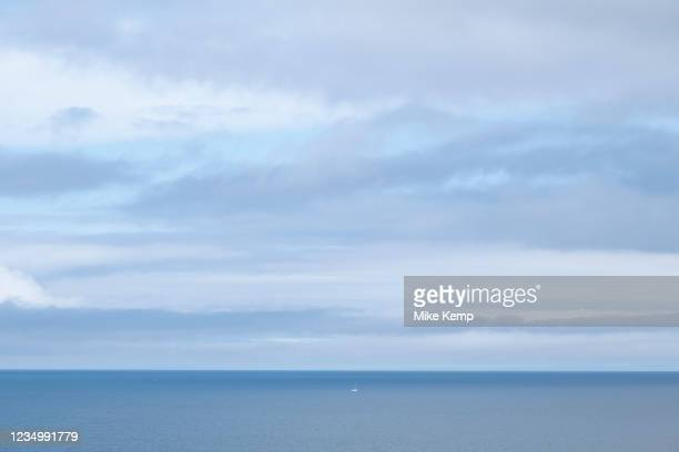 Seascape looking out over a blue sea and sky on 19th August 2021 in Mwnt, Pembrokeshire, Wales, United Kingdom. In the distance a small boat sits...
