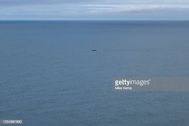 Seascape looking out over a blue sea and sky on 19th August 2021 in Mwnt, Pembrokeshire, Wales, United Kingdom. In the distance a small fishing boat...