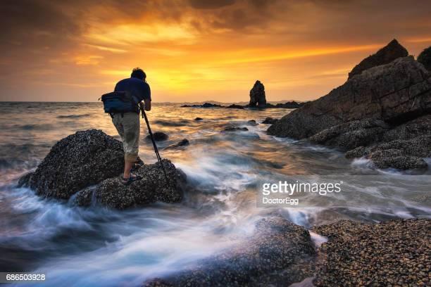 seascape photographer on the rocks at twilight, chonburi, thailand - nikon stock pictures, royalty-free photos & images