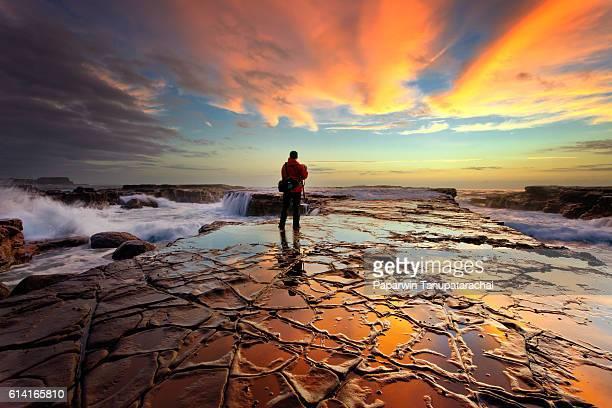 Seascape photographer taking stunning sunrise