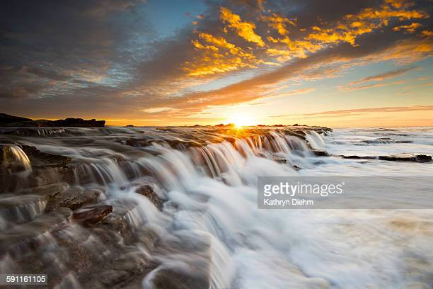 Seascape waterfall with sun star