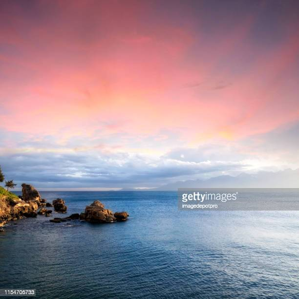 seascape with rocky shore over cloudy sunset sky - romantic sunset stock pictures, royalty-free photos & images