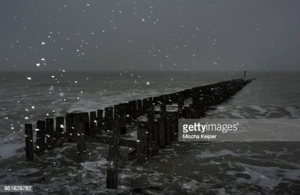 Seascape with snow at breakwater, Domburg, Zeeland, Netherlands