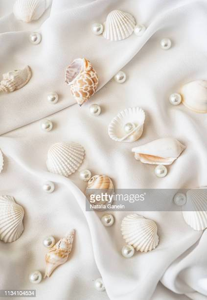 seashells and pearls on white silk - pearl jewelry stock pictures, royalty-free photos & images