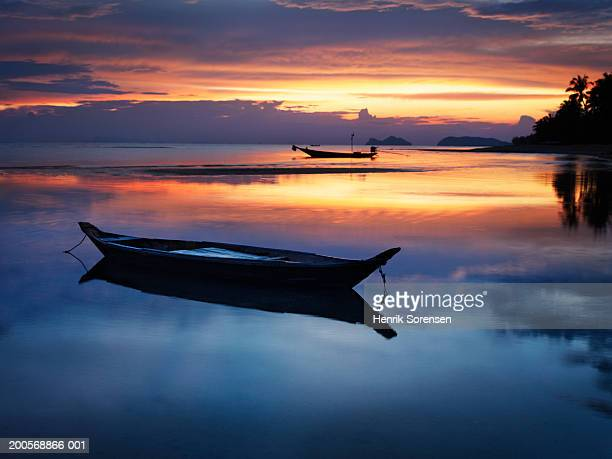Seashore with longtail boats at sunset