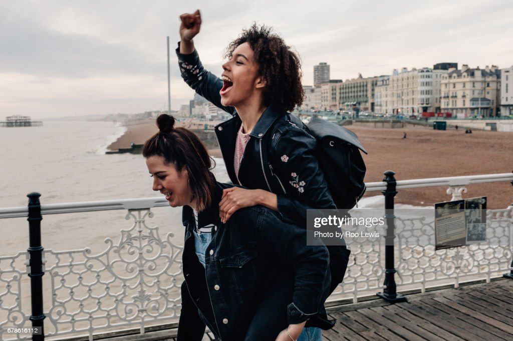 Mixed race couples on a day out at seaside having fun.