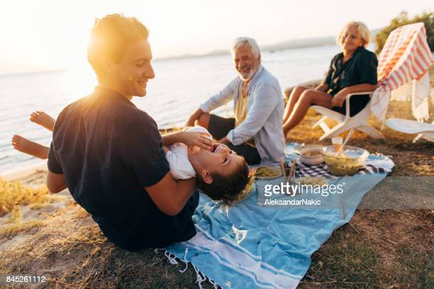 seaside picnic with family - candid beach stock photos and pictures