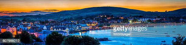 Seaside resort town ocean bay illuminated at sunset Swanage Dorset