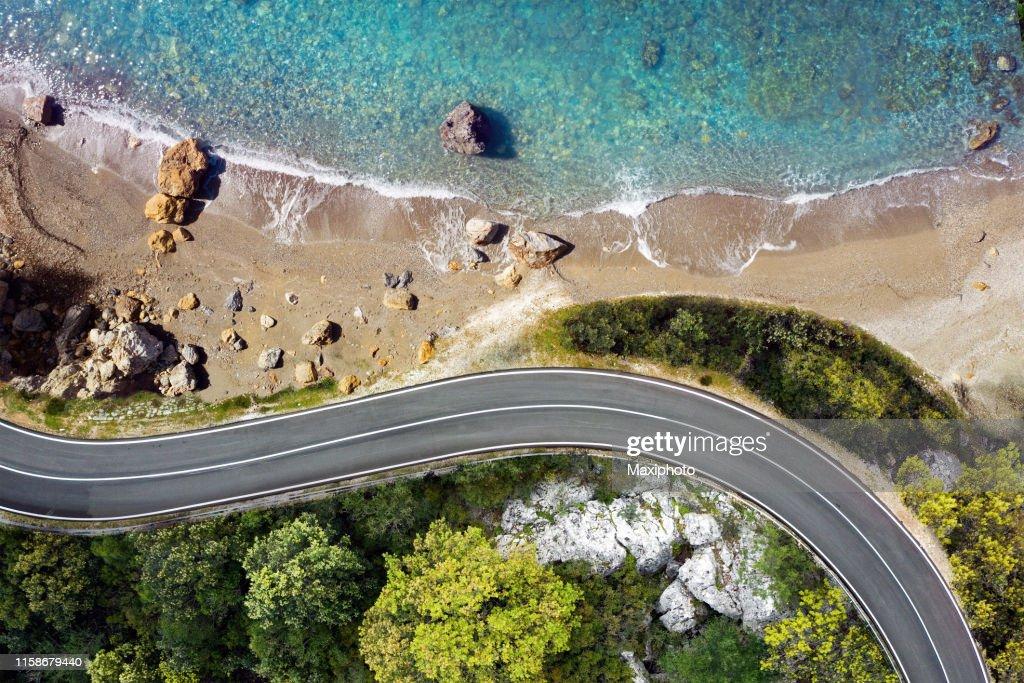 Küstenstraße nähert sich einem Strand, von oben gesehen : Stock-Foto