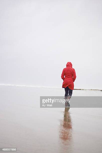 seaside stroll on a rainy day - coat stockfoto's en -beelden