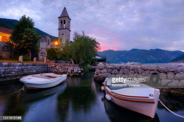 seaside town. boats in the foreground, an old stone tower in the background. - kotor bay stock pictures, royalty-free photos & images